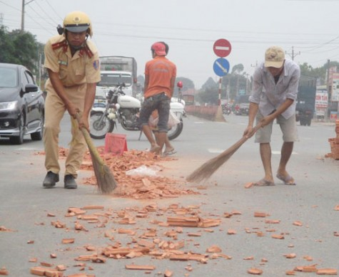 Cảnh sát giao thông dọn gạch đổ giữa đường