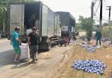 Người dân giúp tài xế gom hàng trăm thùng bia đổ xuống đường